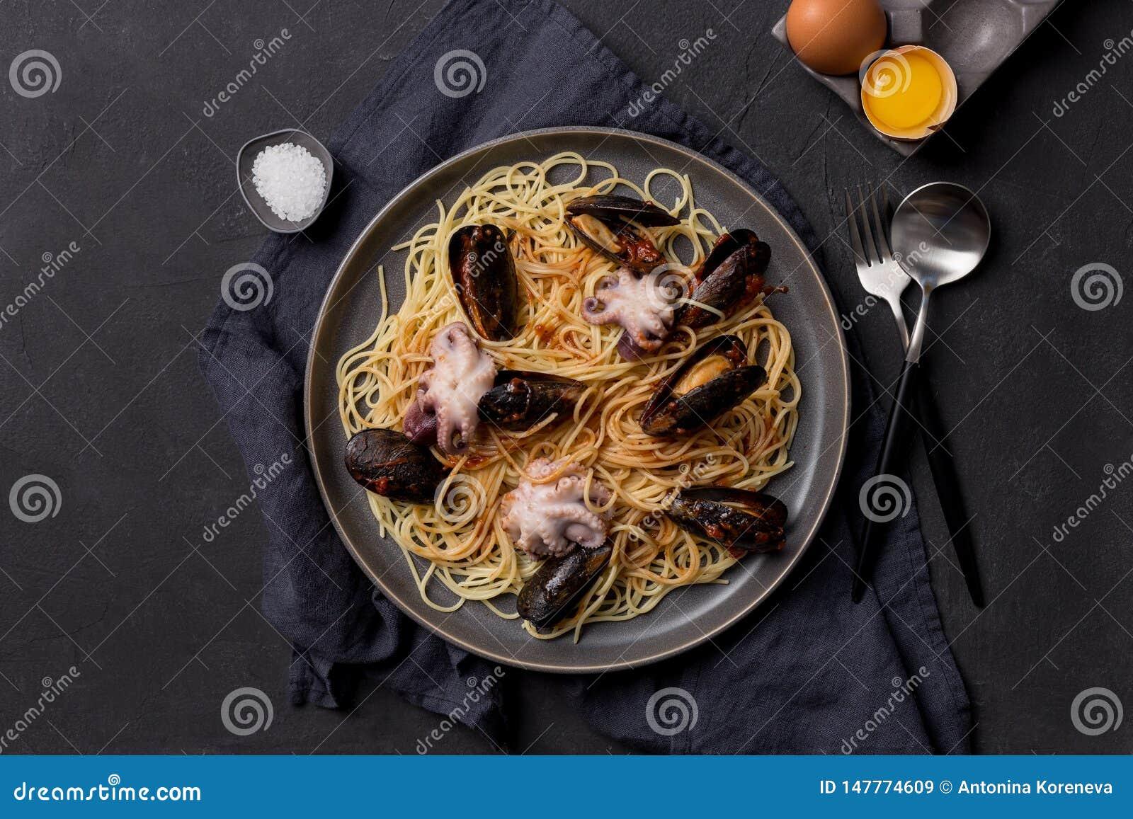 Smaklig pasta med bläckfisken och musslor på grå bakgrund