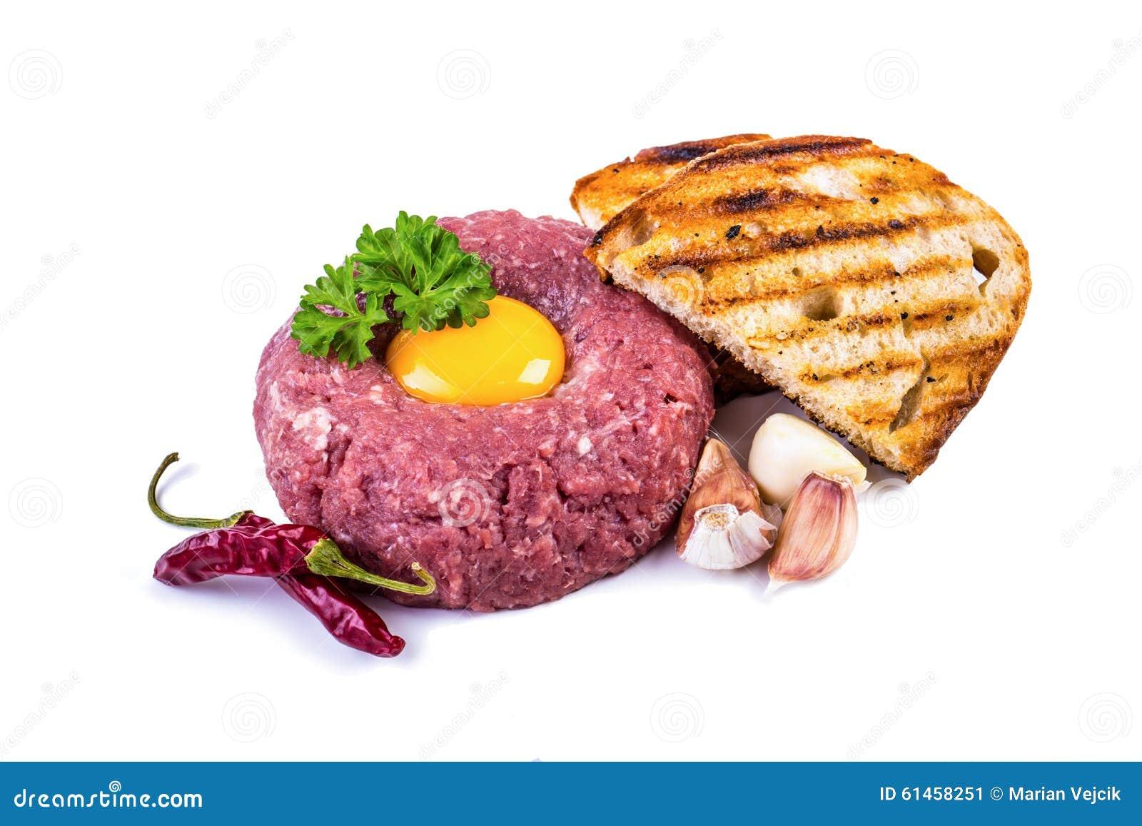Smaklig tartarbiffstek Klassisk tartarbiffstek över vit Ingredienser: Garnering för ört för chili för vitlök för ägg för peppar f