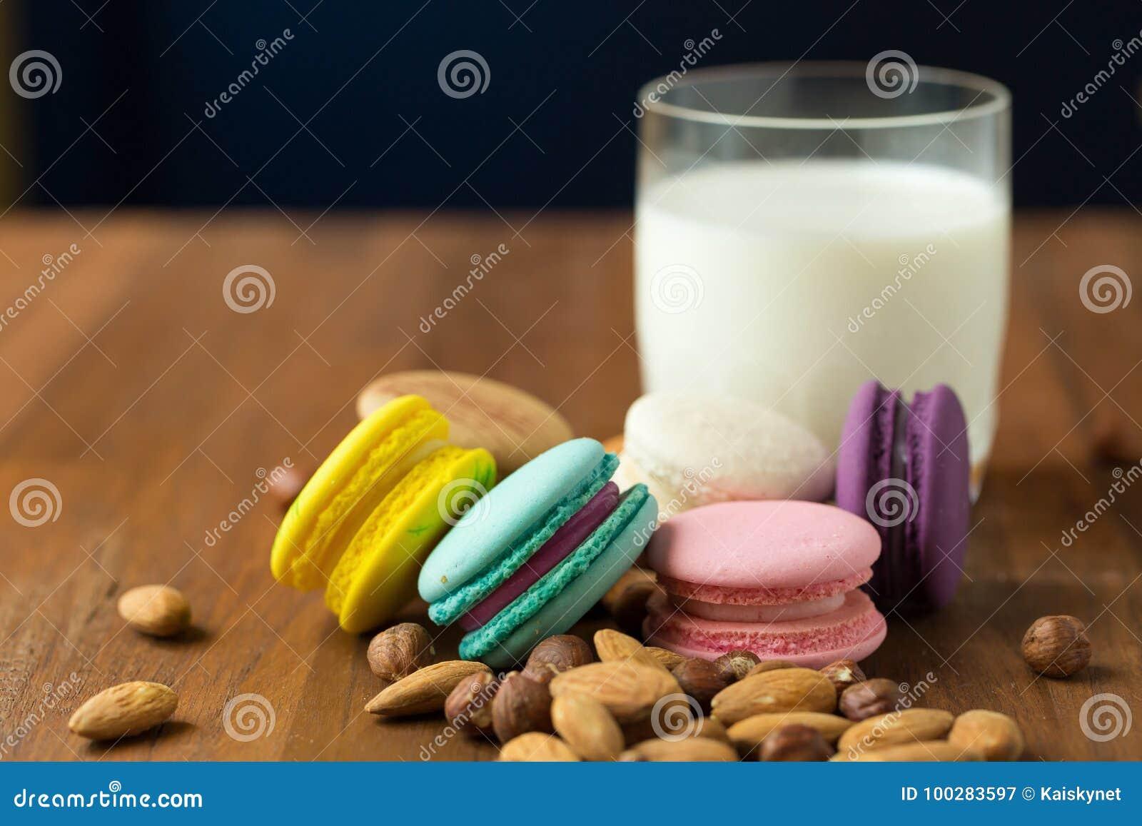 Smakliga makron och koppen av mjölkar med mandeln på träbakgrund