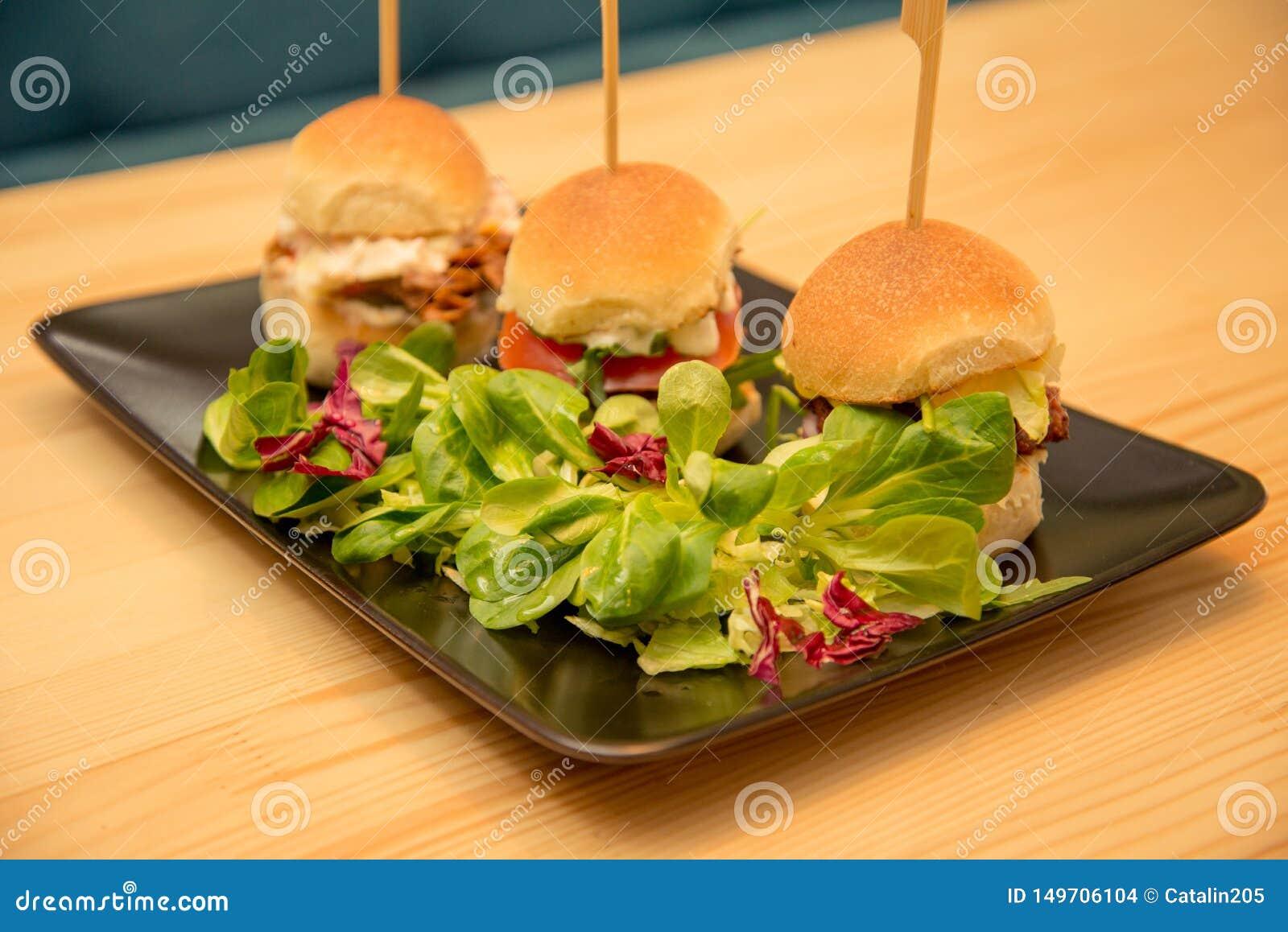 Smakliga mini- hamburgare f?r n?rbild med sallad p? bistrotabellen