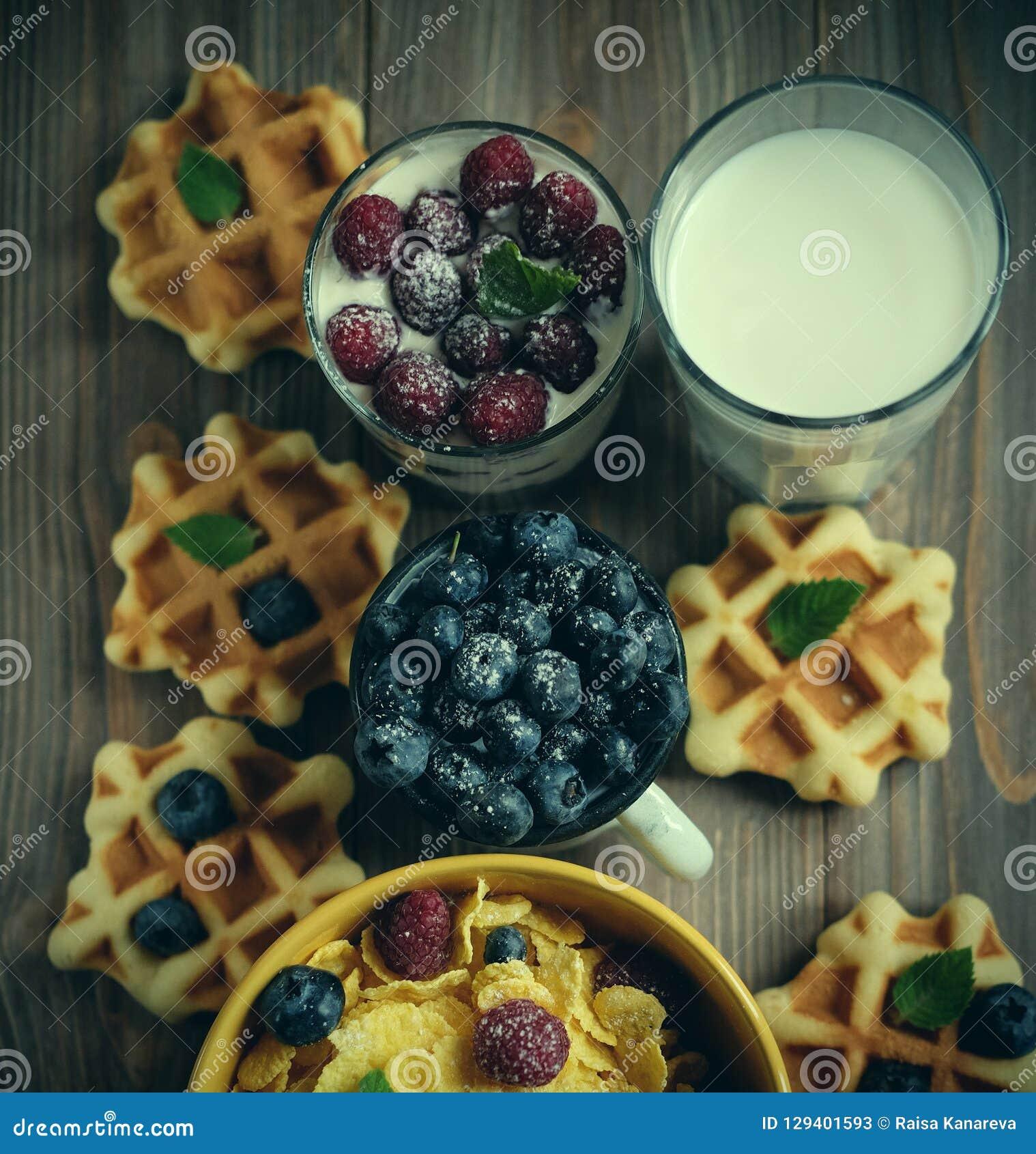 Smakowici cornflakes z malinkami i czarnymi jagodami na błękitnym tle Opłatki i mleko