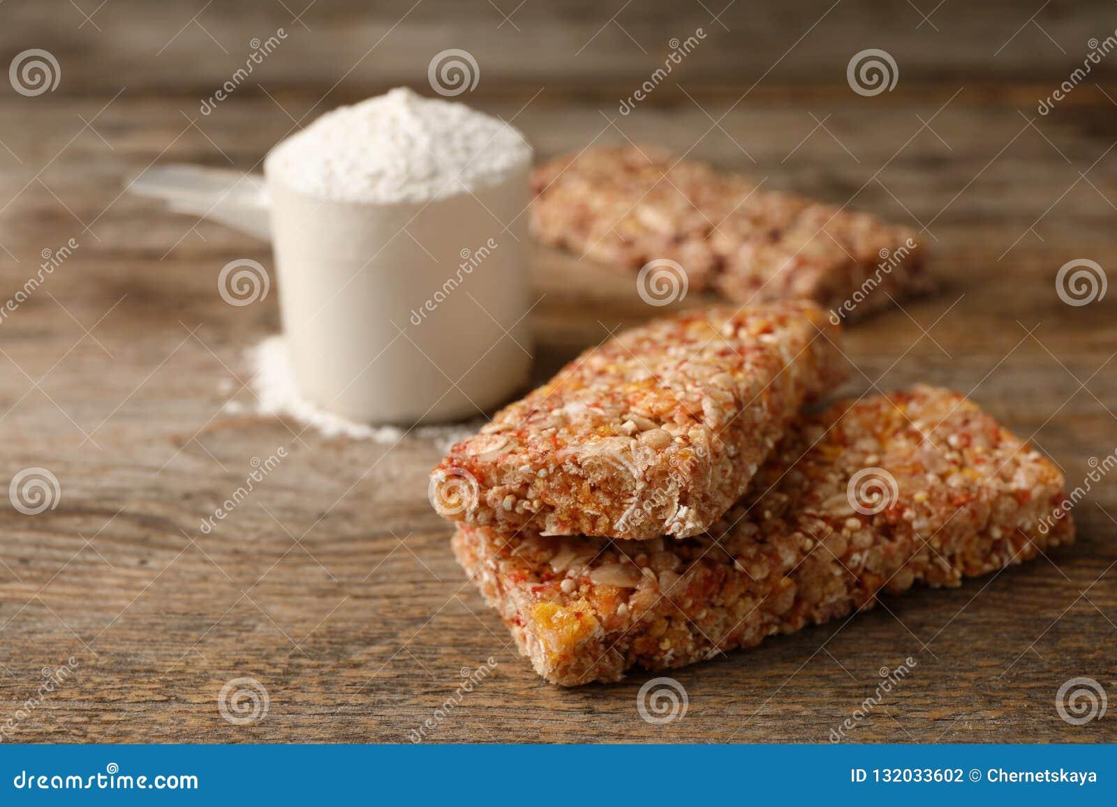 Smakowici proteina bary i miarka proszek na drewnianym stole