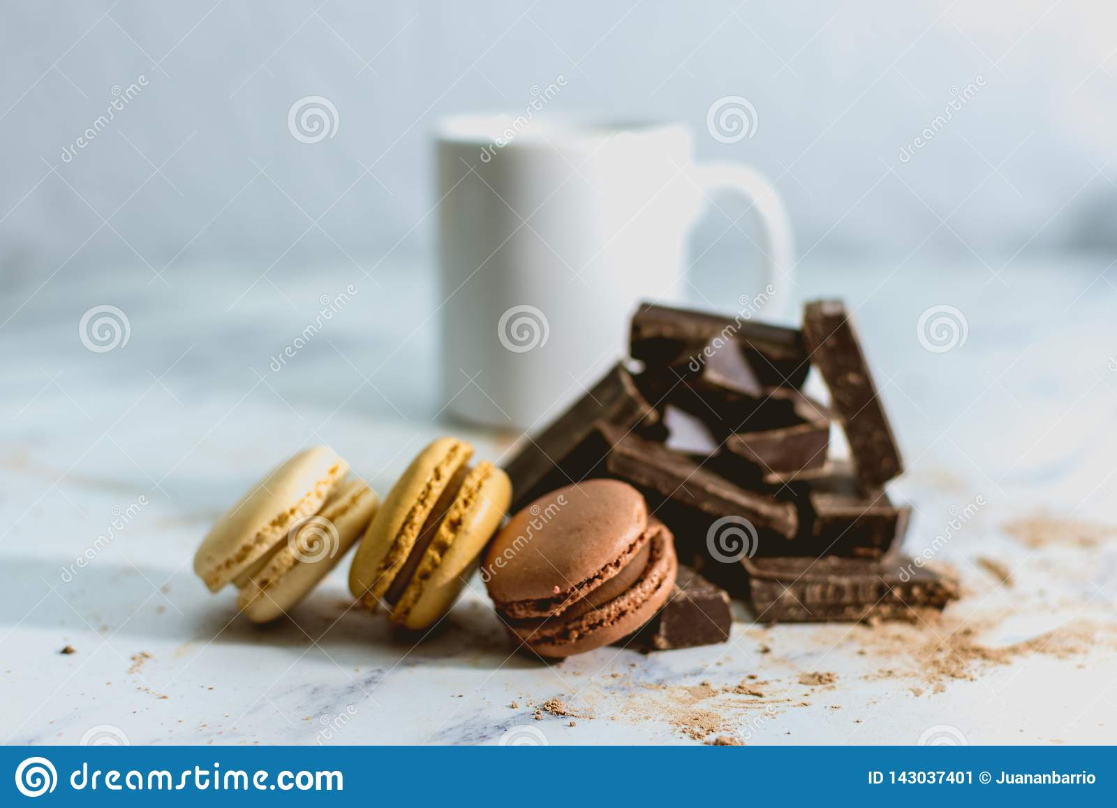 Smakowici słodcy macarons z filiżanka kawy na tle