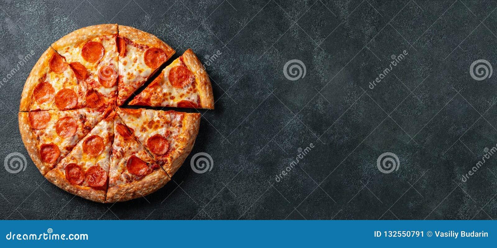 Smakowita pepperoni pizza i kulinarny składników pomidorów basil na czerni betonujemy tło Odgórny widok gorąca pepperoni pizza z