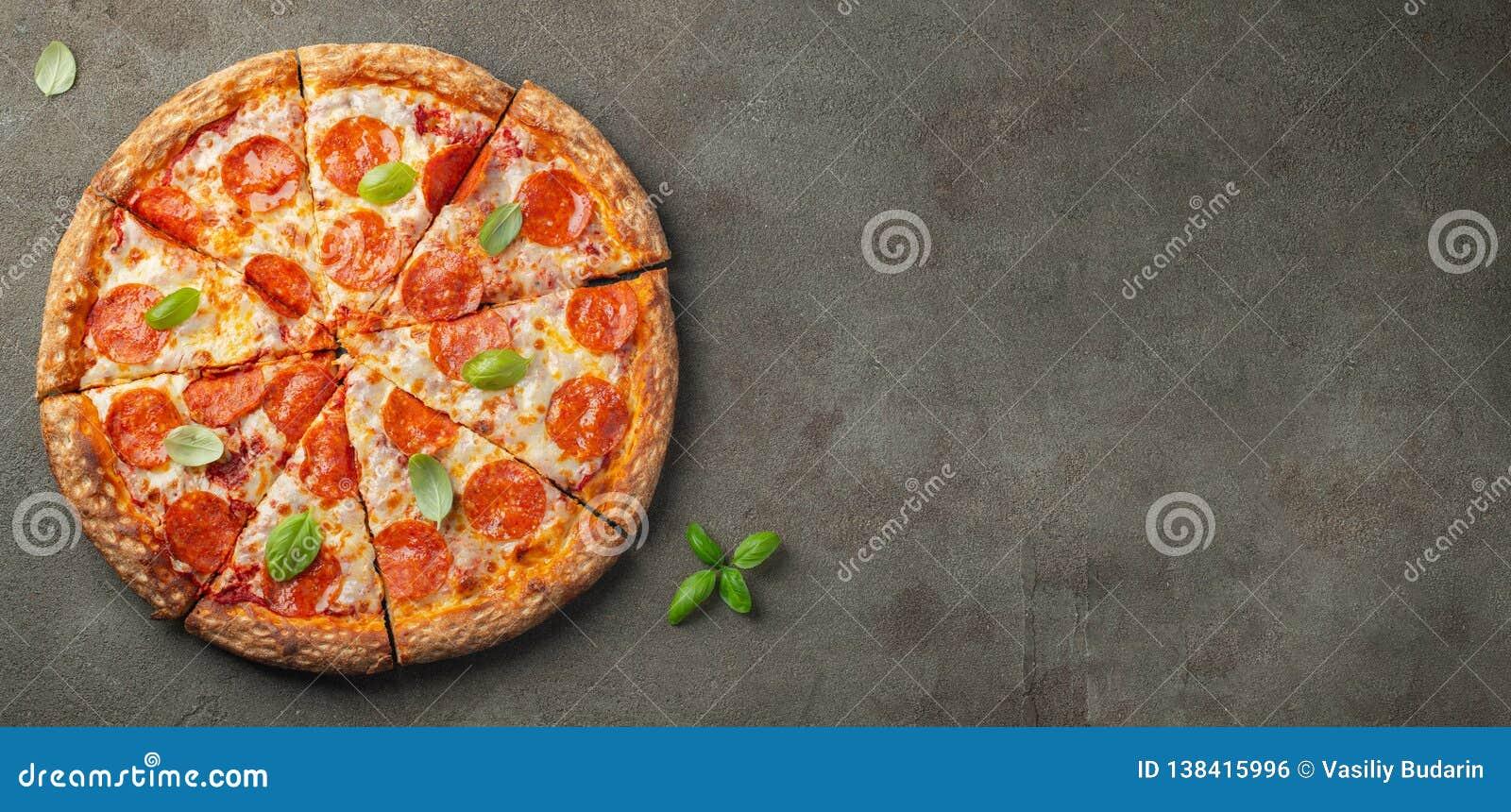 Smakowita pepperoni pizza z basilem na brązu betonu tle Odgórny widok gorąca pepperoni pizza Z kopii przestrzenią dla teksta Mies