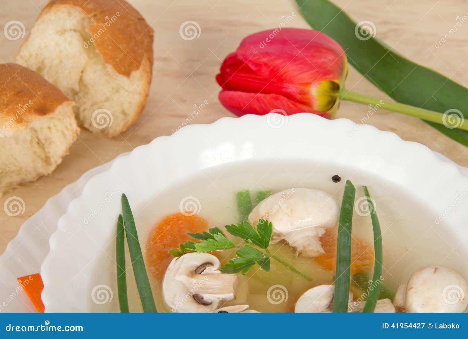 Smakowita pieczarkowa polewka, plasterki chleb i czerwień tulipan,