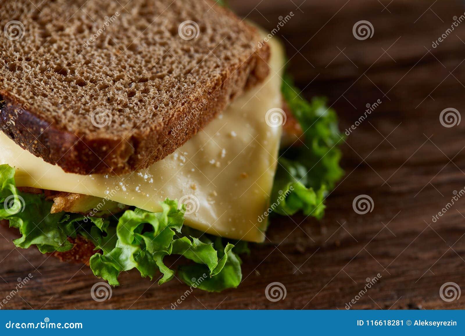 Smakowite i świeże kanapki na tnącej desce nad ciemnym drewnianym tłem, zakończenie