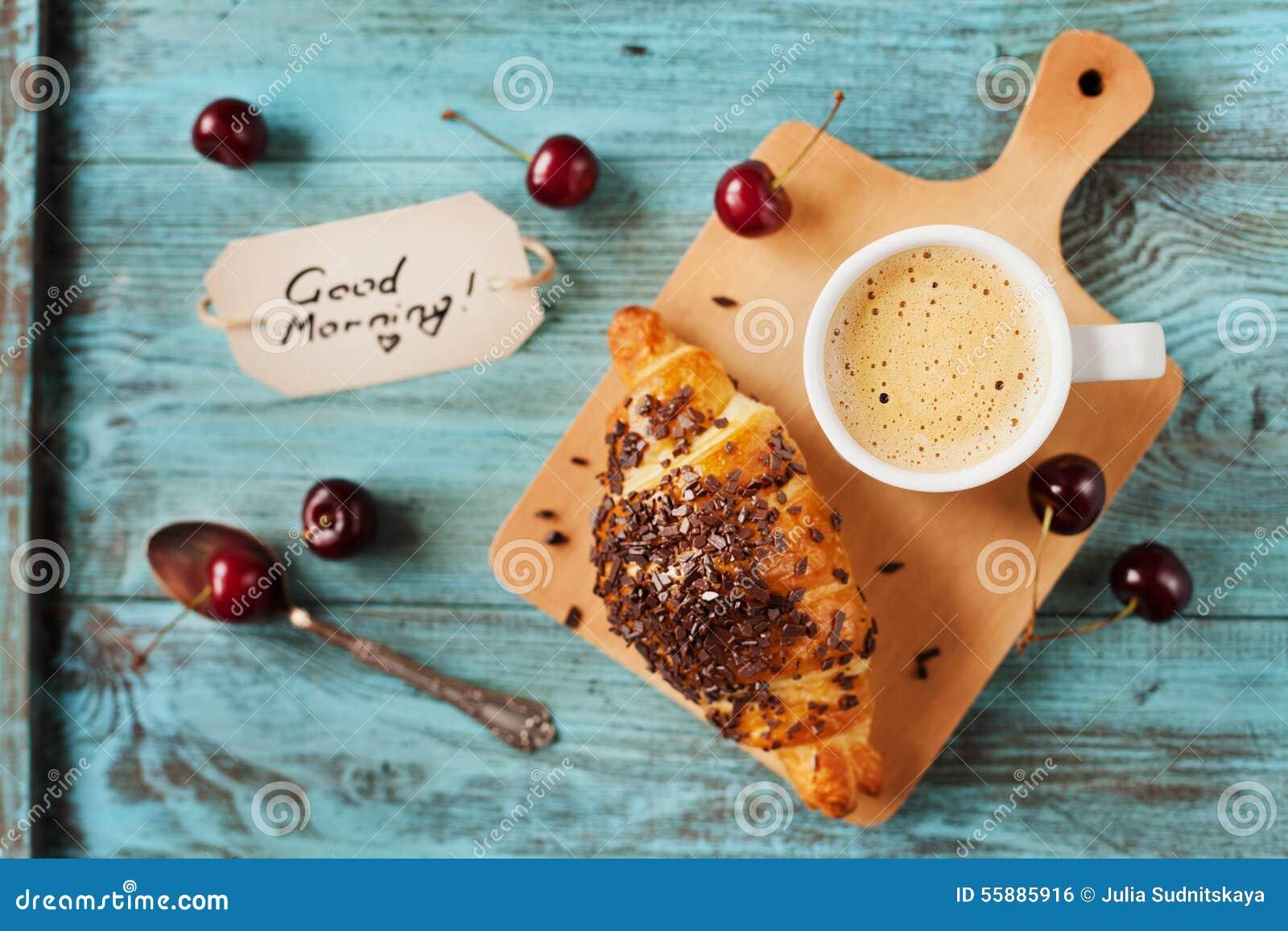 Smakowity śniadanie z świeżym croissant, kawą, wiśniami i notatkami na drewnianym stole,
