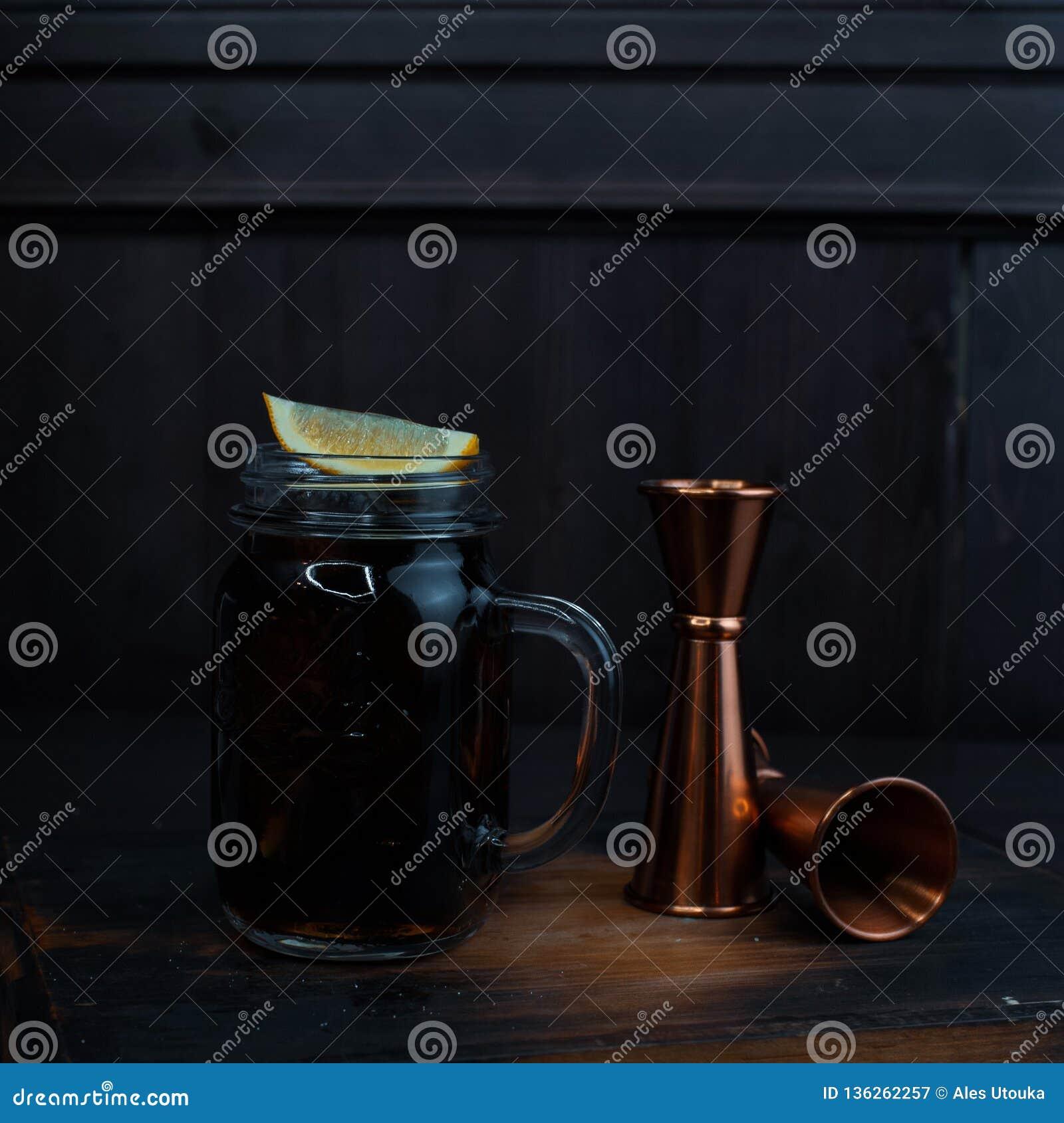 Smakowity alkoholiczny koktajl z lodem, czarnym rumem i koka-kola, cytryna plasterki stoi na drewnianym stole w restauracji