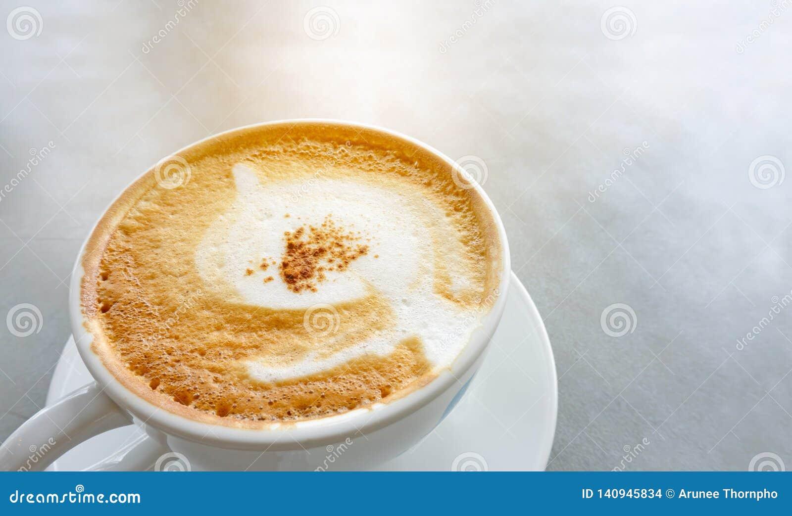 Smakowity pić, filiżanka dekorująca z puszystym mlekiem cappuccino kawa, białego i brązu spieniamy w białej ceramicznej filiżance