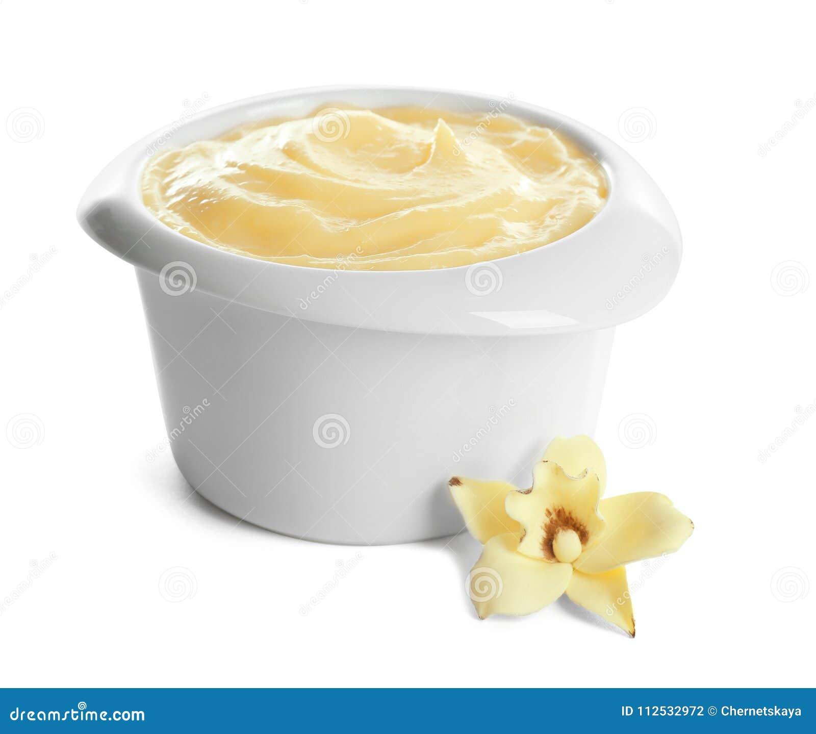 Smakowity waniliowy pudding w ramekin i kwiacie na białym tle