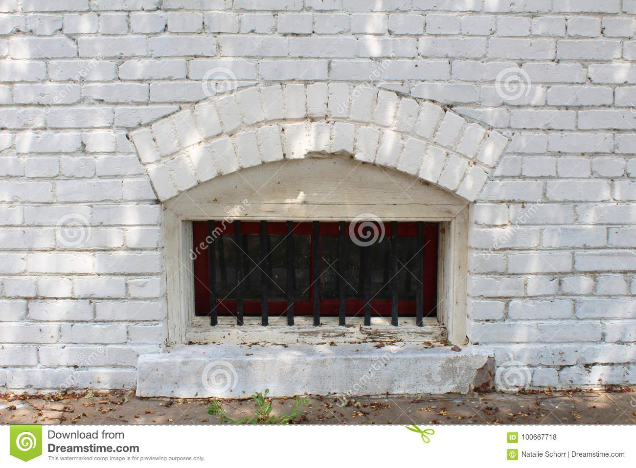 Small Arched Basement Window With Bars In A White Brick ...
