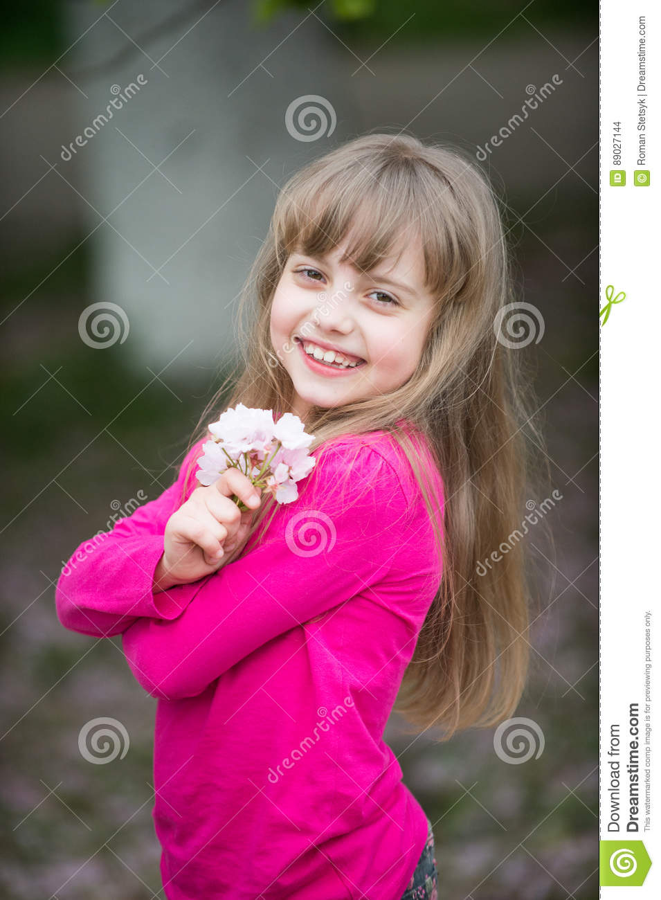 small baby girl with smiling face holding pink sakura blossom stock