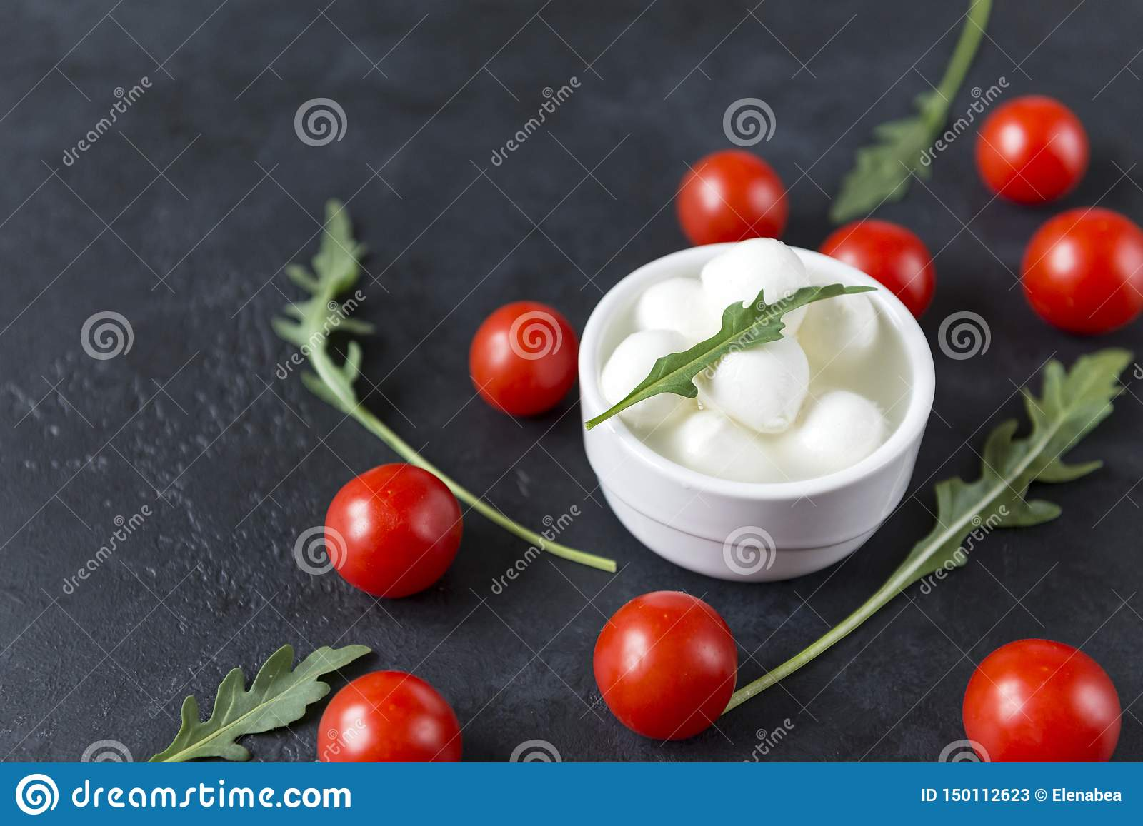 Small balls of mozzarella in a bowl with arugula , cherry tomatoes on a black background