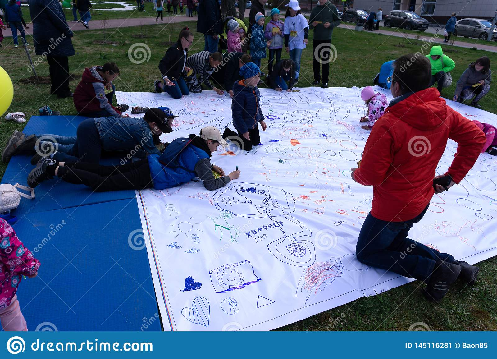 Small beautiful girl paints on apaper on floor . Russia Berezniki 26 may 2019