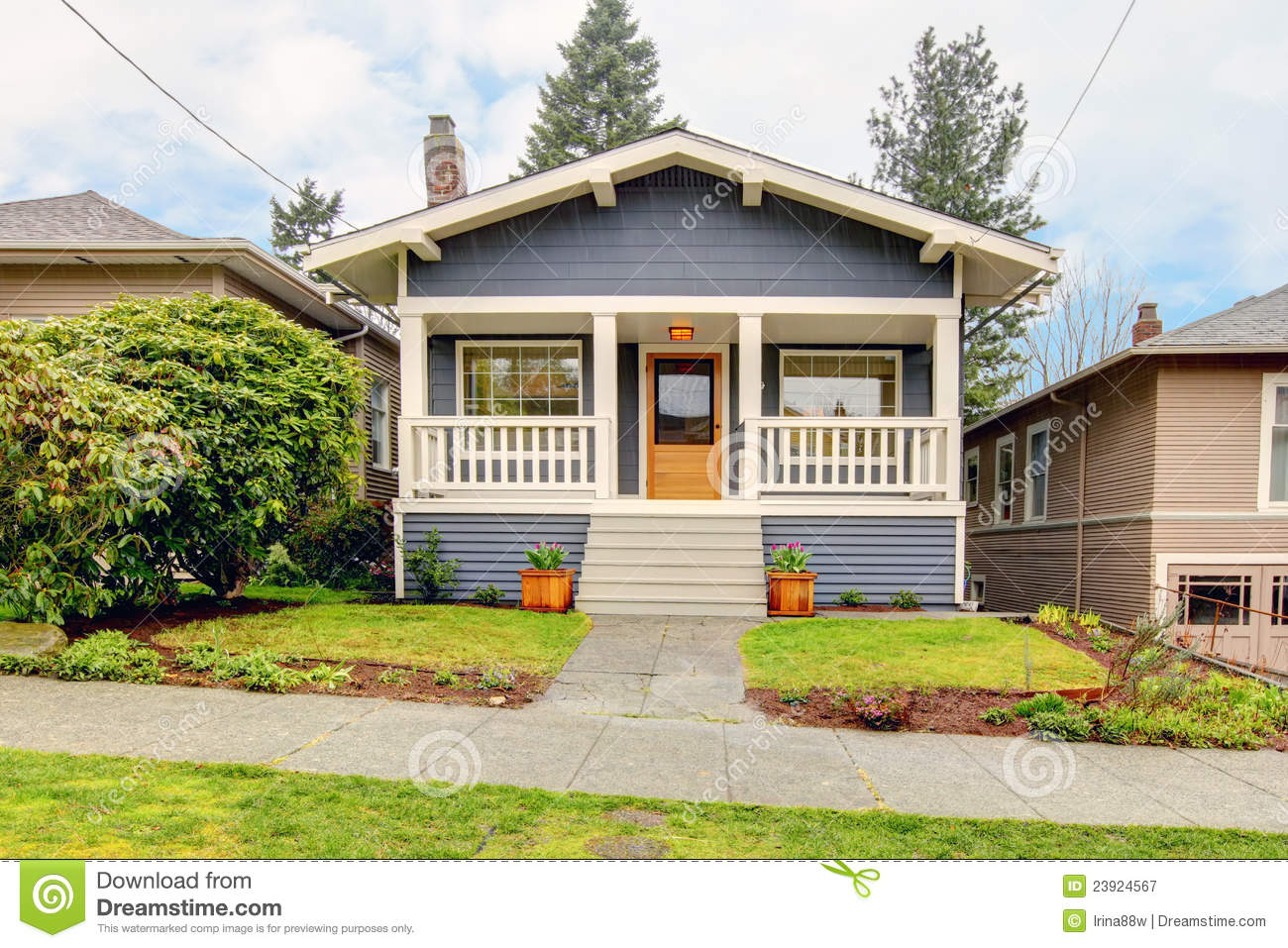 Small simple blue grey craftsman style house with white porch
