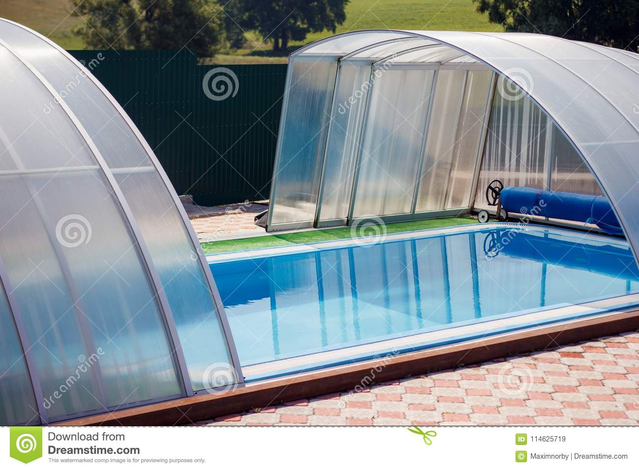 A Small Blue Swimming Pool With Water Under A Canopy In The Stre