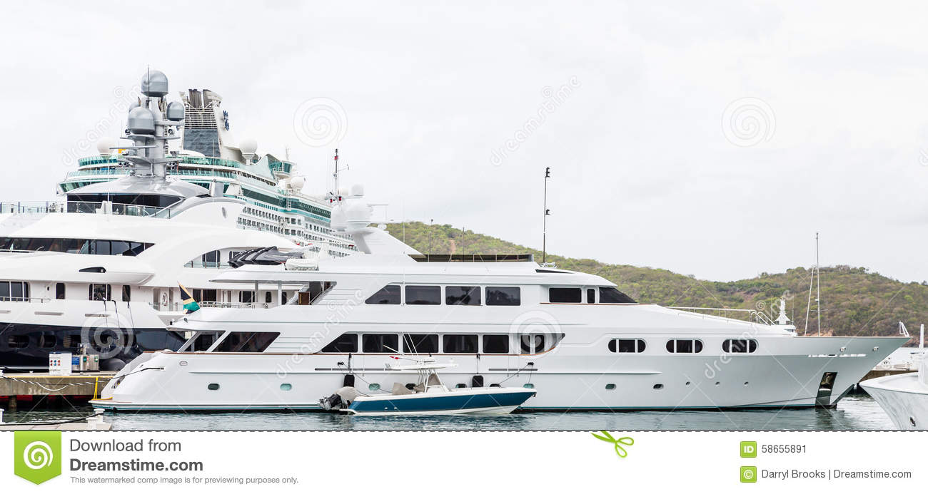 Small boat by massive yacht by cruise ship stock photo for Luxury small cruise lines