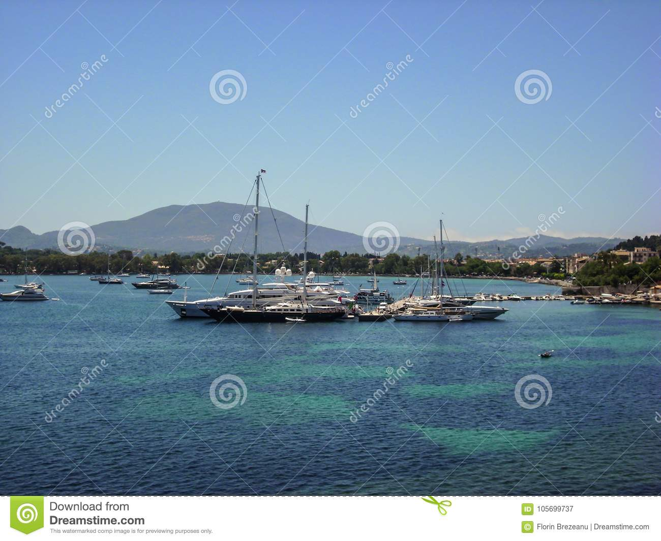 Small boats and yachts in the ionian sea with green vegetation. The beautiful island of Corfu, Greece.