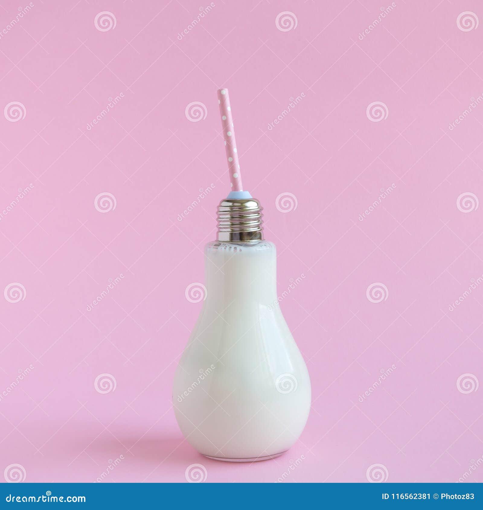 Glass bulb bottle of milk on rose background.