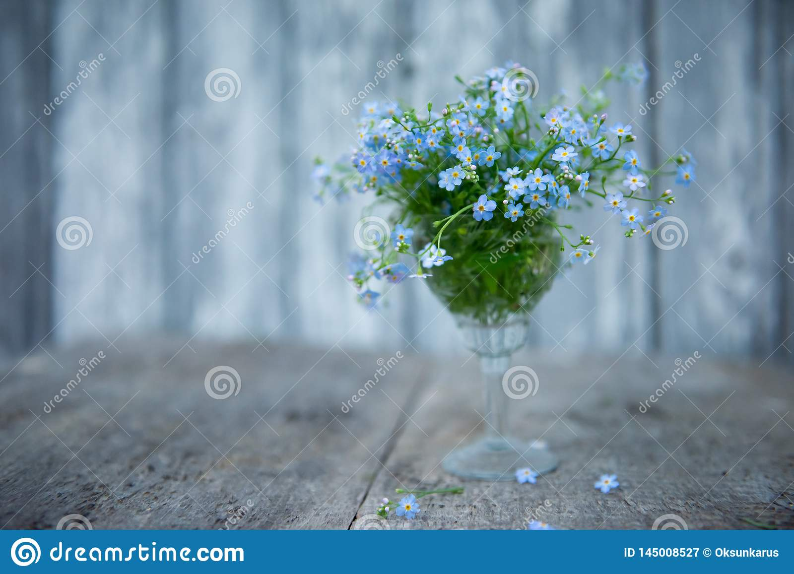 A small bouquet of forget-me-nots in a crystal glass on a blurred background of boards painted with blue paint and a few flowers o