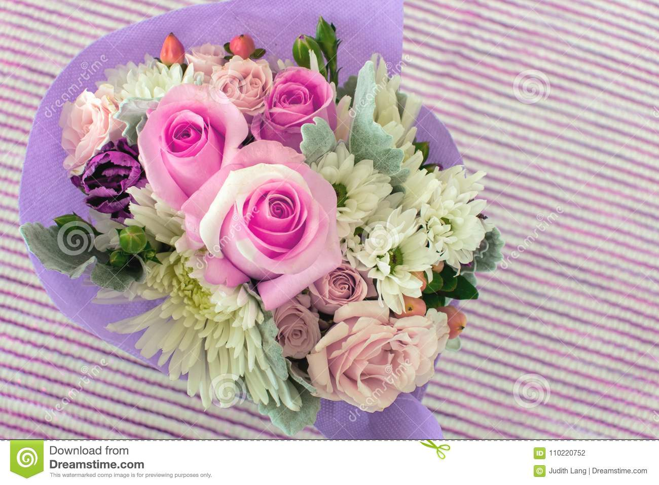 A small bouquet of pretty pink miniature roses on striped background.