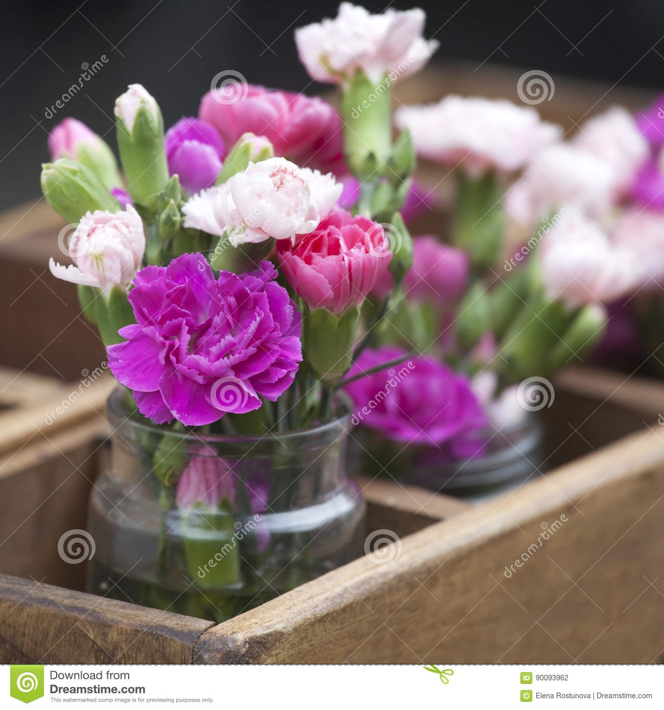 the small bouquets of pink and white carnations in a wooden box