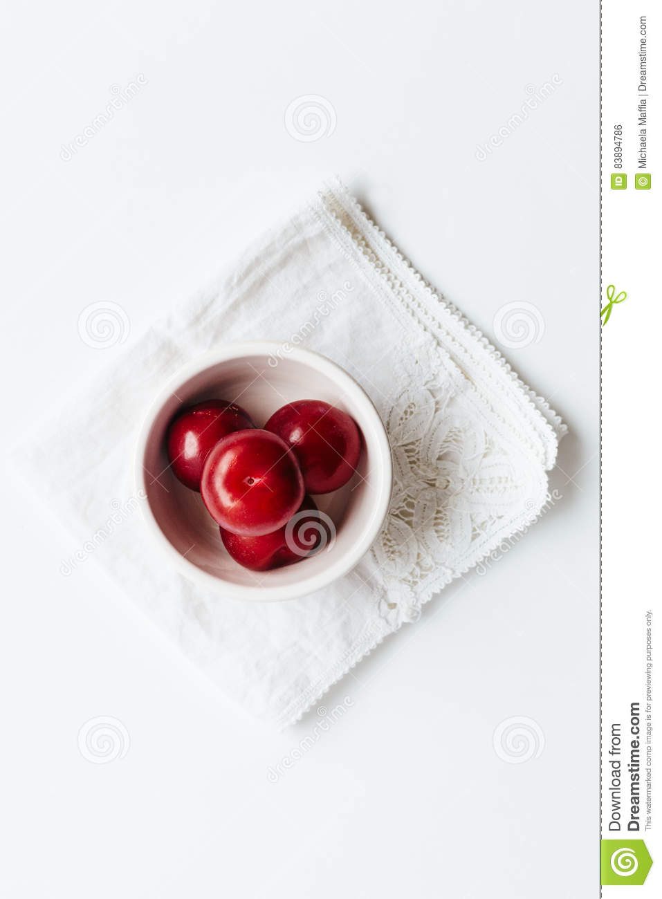 Small bowl of red plums on white vintage napkin
