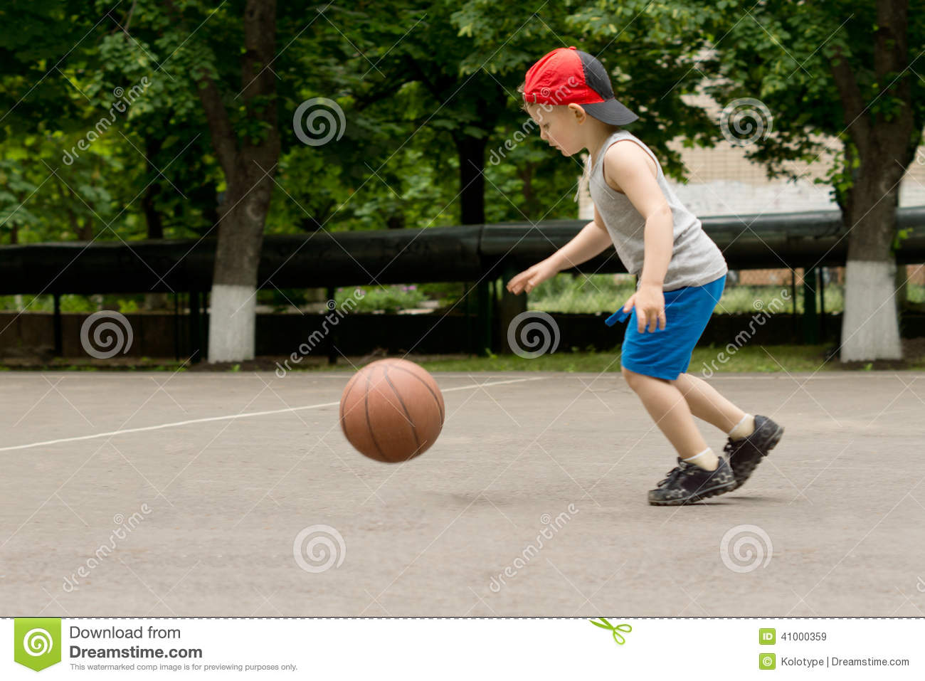 Small Boy Bouncing A Basketball On A Court Stock Photo