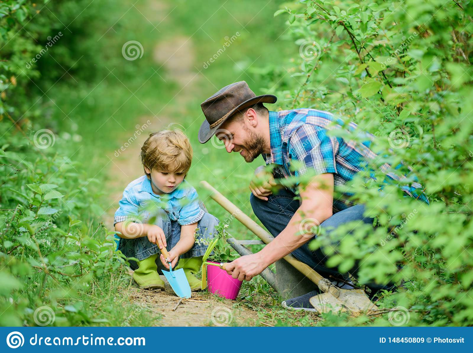 Small boy child help father in farming. Eco farm. father and son in cowboy hat on ranch. hoe, pot and shovel. Garden