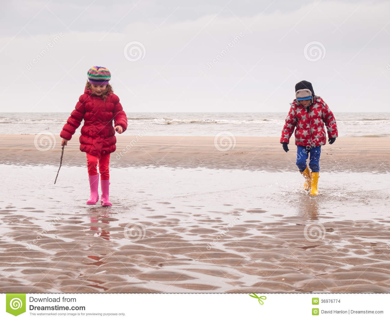 a71a935e31 Small boy and girl in winter clothing and rubber boots spalshing in a tidal  pool on a winter beach