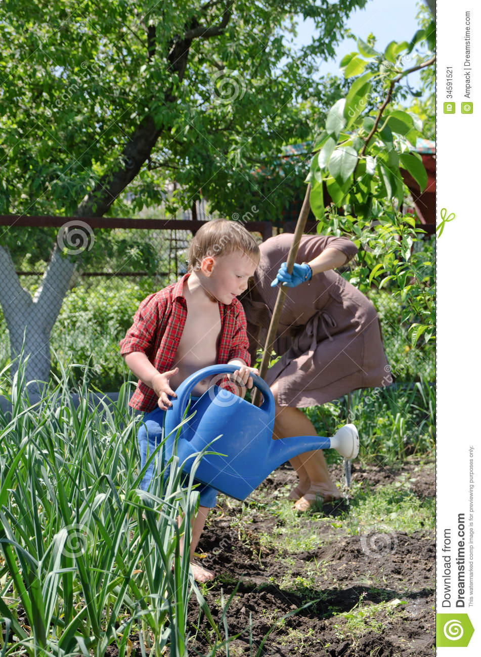 Small boy helping mum water the vegetable garden stock for Watering vegetable garden