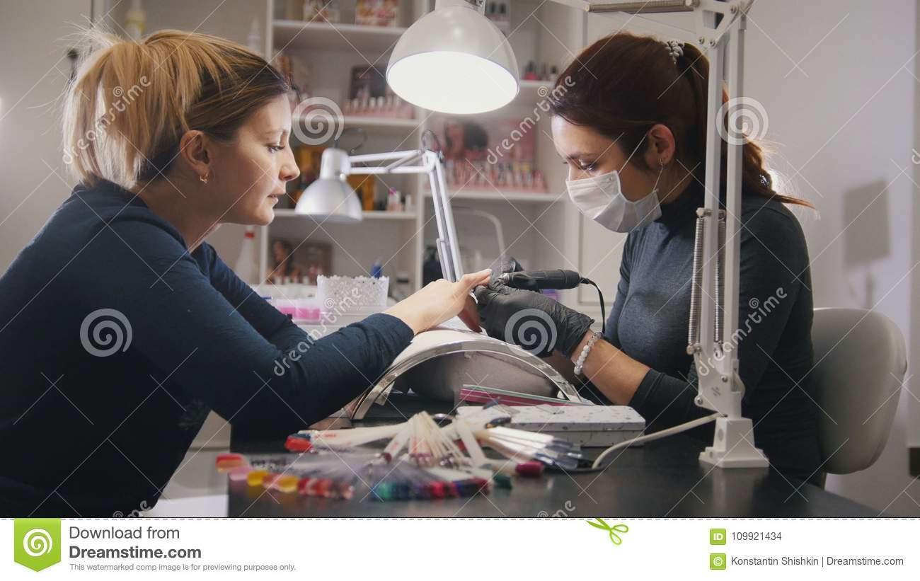 Small business - manicurist - nail master in medical mask doing professional manicure