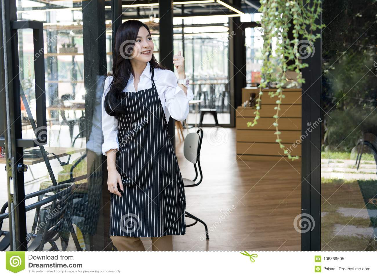 small business owner standing at coffee shop. female barista wearing apron smiling at cafe. food service, restaurant concept.