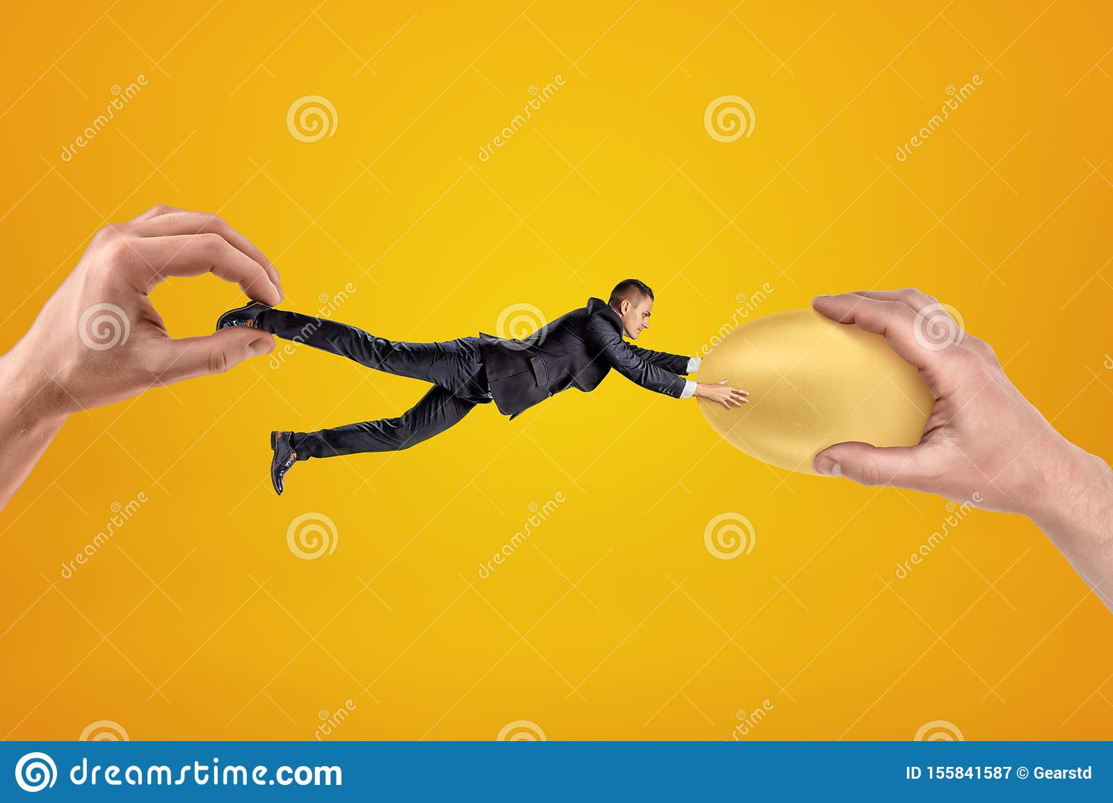 Small businessman being pulled in opposite directions by two big hands, and clutching with his both hands at gold egg in