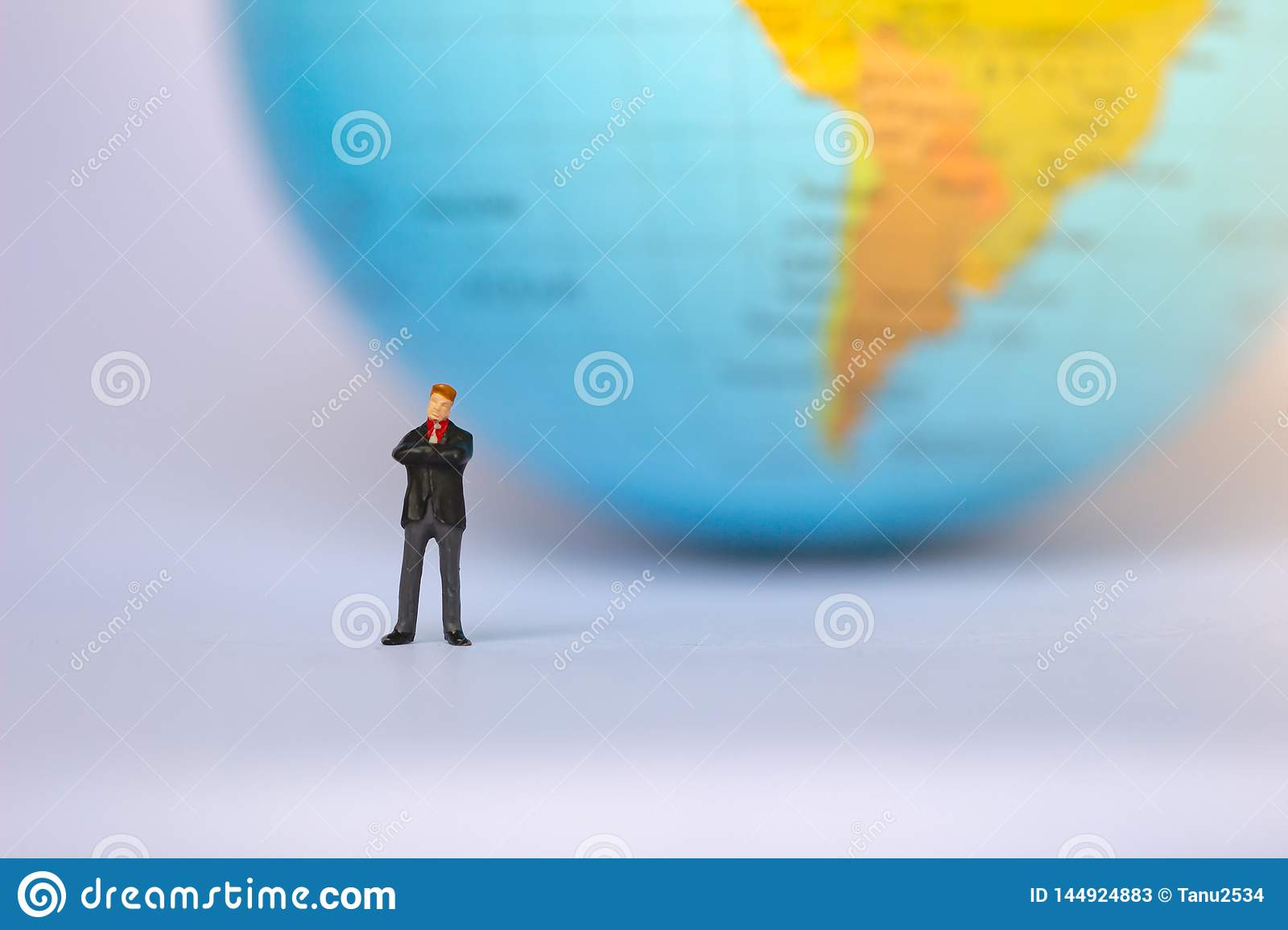 Small businessman figures standing on turning point on earth background.