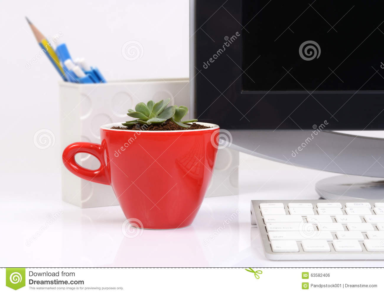 Small Cactus In Red Ceramic Cup On Office Desk.