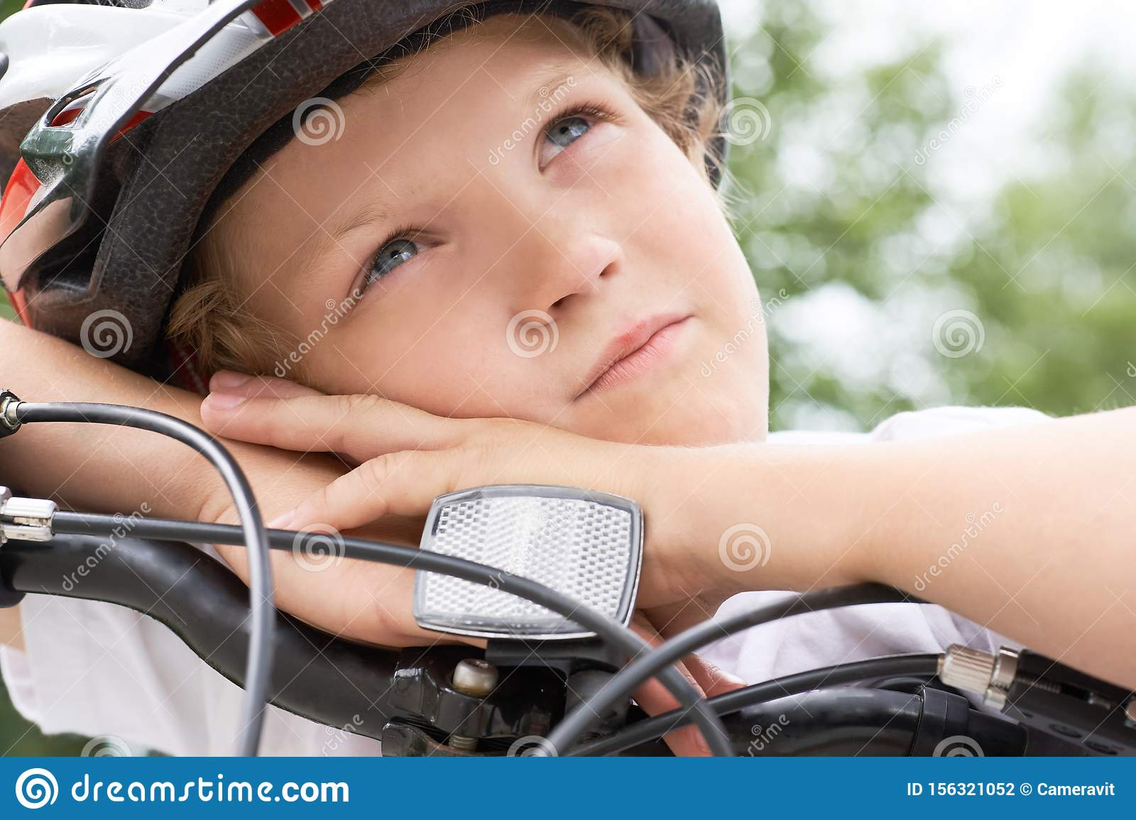 Small Caucasian boy cyclist in protective helmet put his head on the handlebar of the bike posing for the camera. Boy