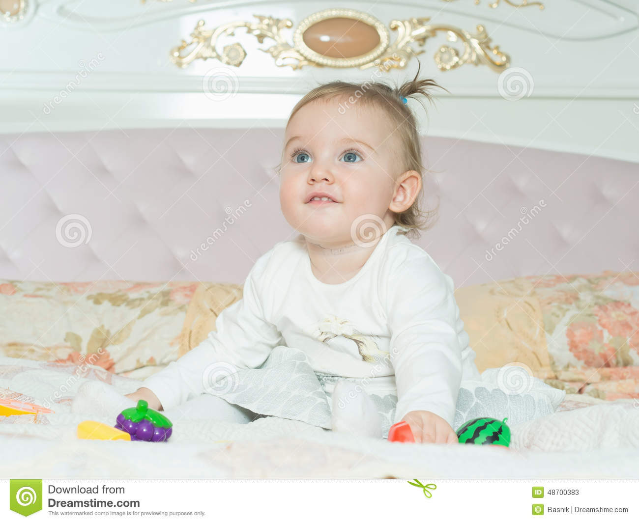 Small caucasian child girl play with toys on the bed at home