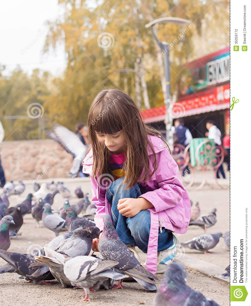 Small caucasian girl and pigeons