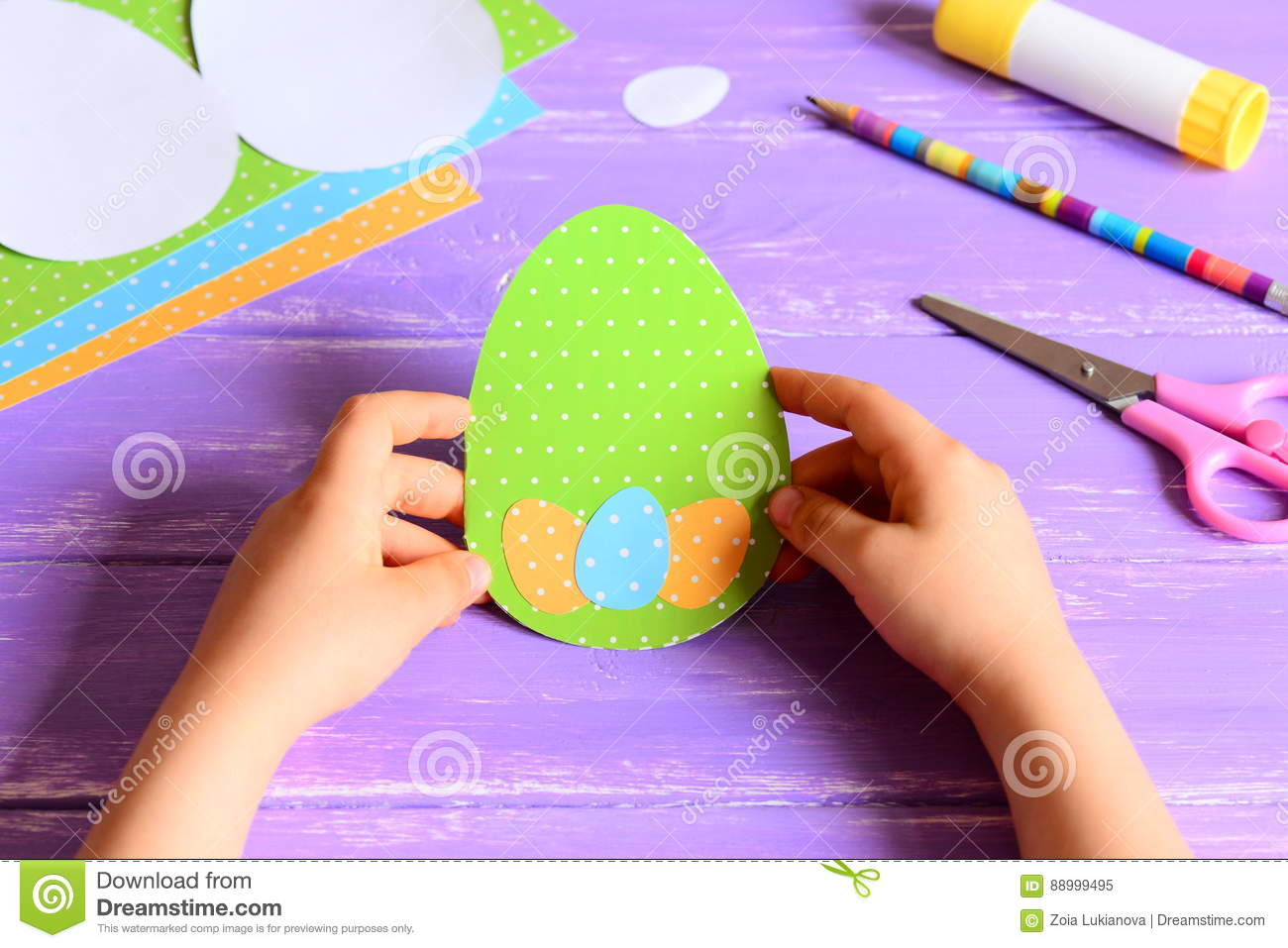 Small child holding a Easter card in hands. Child made Easter greeting card in egg shape
