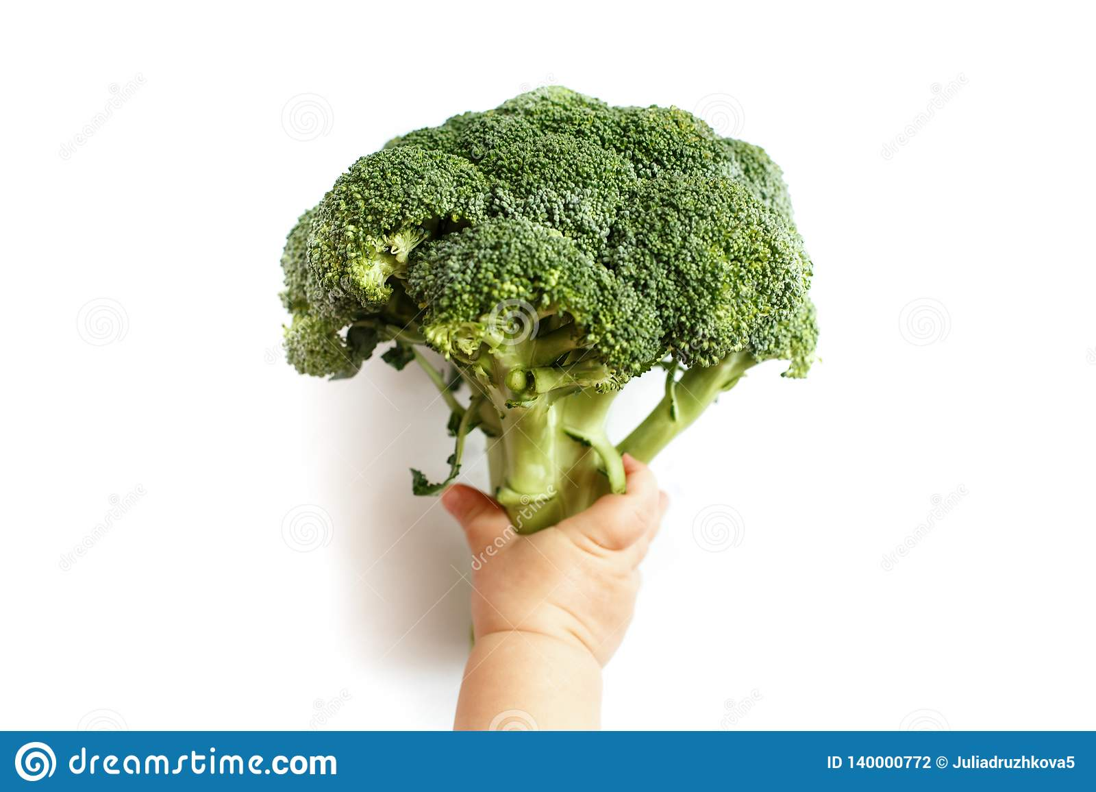 A small child holds broccoli in his hand, he is for a healthy diet