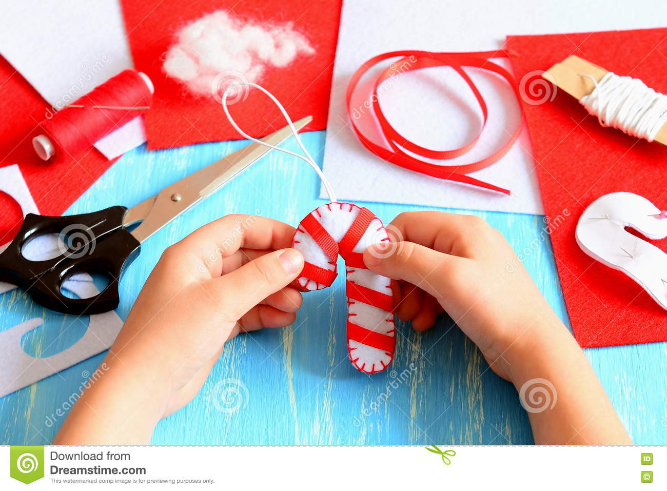 Small Child Holds Christmas Felt Candy Cane In His Hands