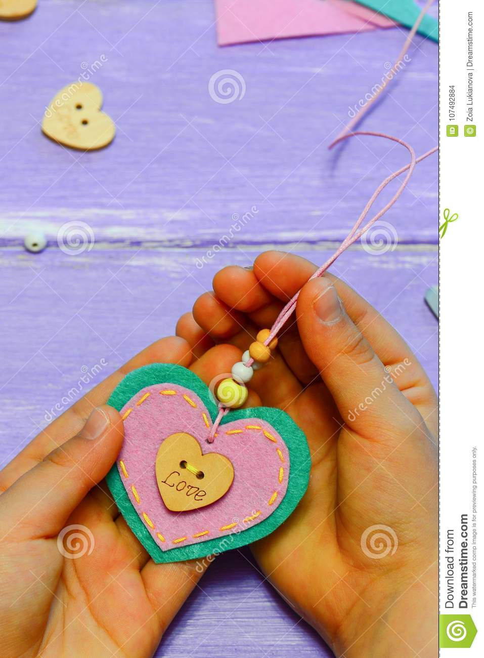 Small Child Holds A Felt Heart Pendant Necklace In His Hands Child