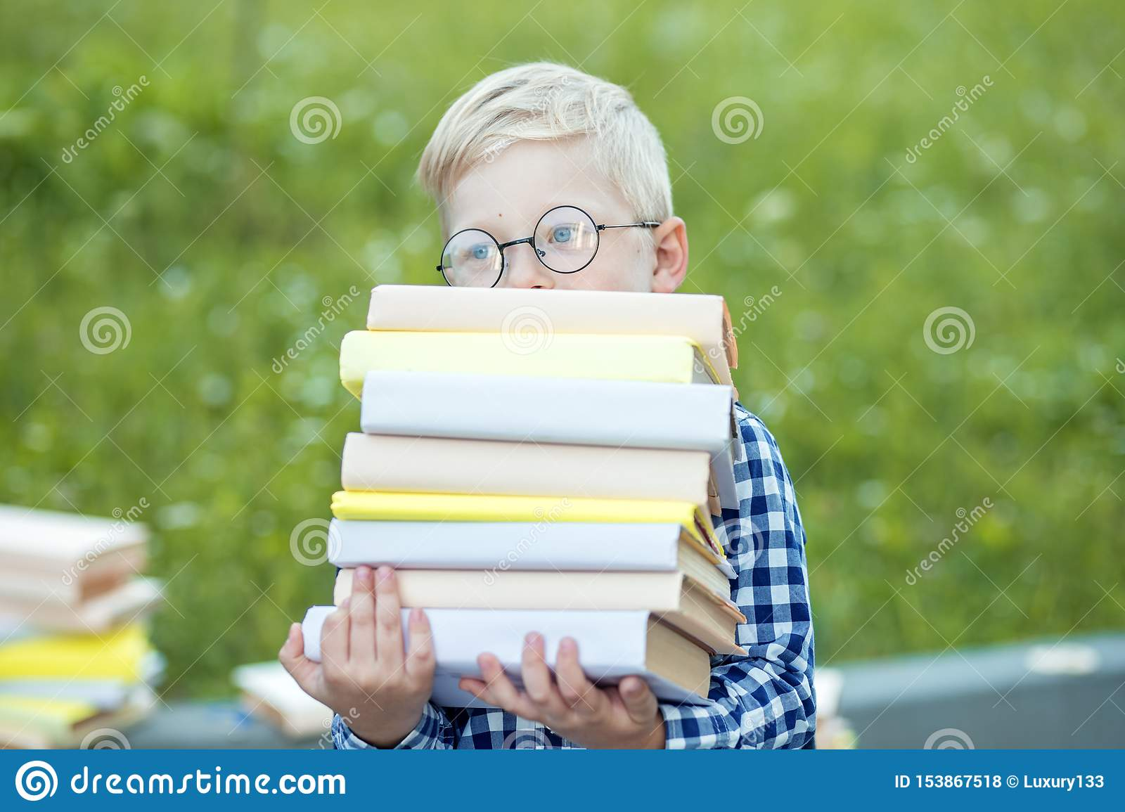 A small child holds many books in their hands. The concept of learning, school, mind, lifestyle and success