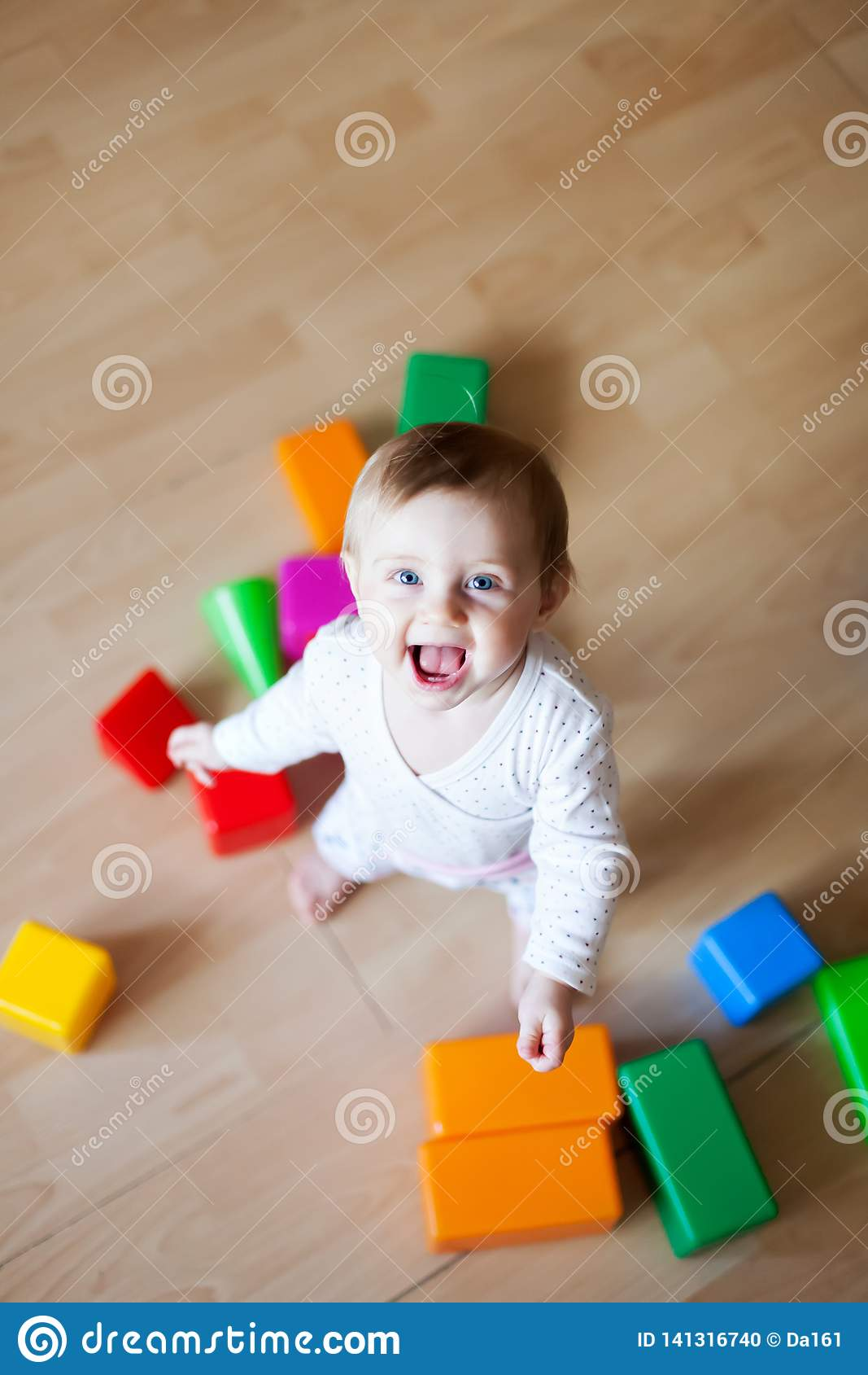 Small child of 9 months playing on floor of house