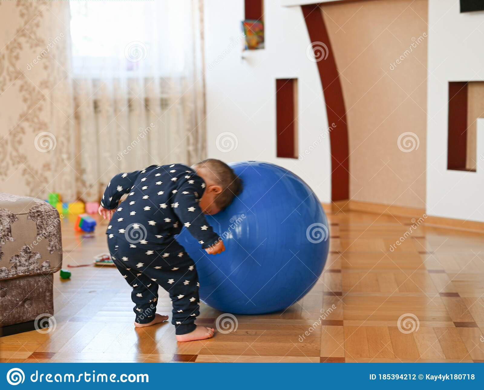 A Small Child Is Playing With A Ball. Baby Banging His ...