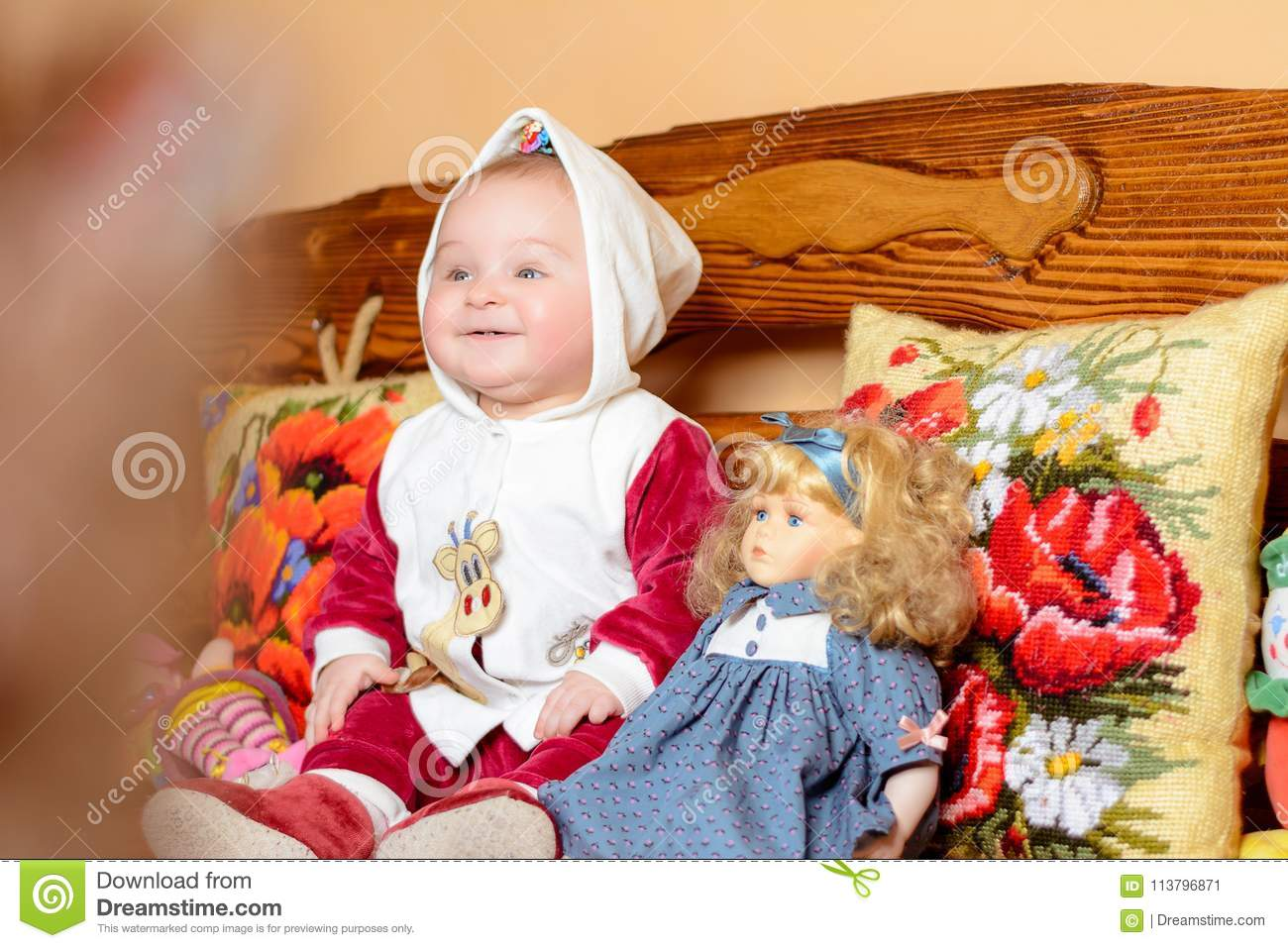 A small child in a shawl sitting on a sofa with embroidered pillows