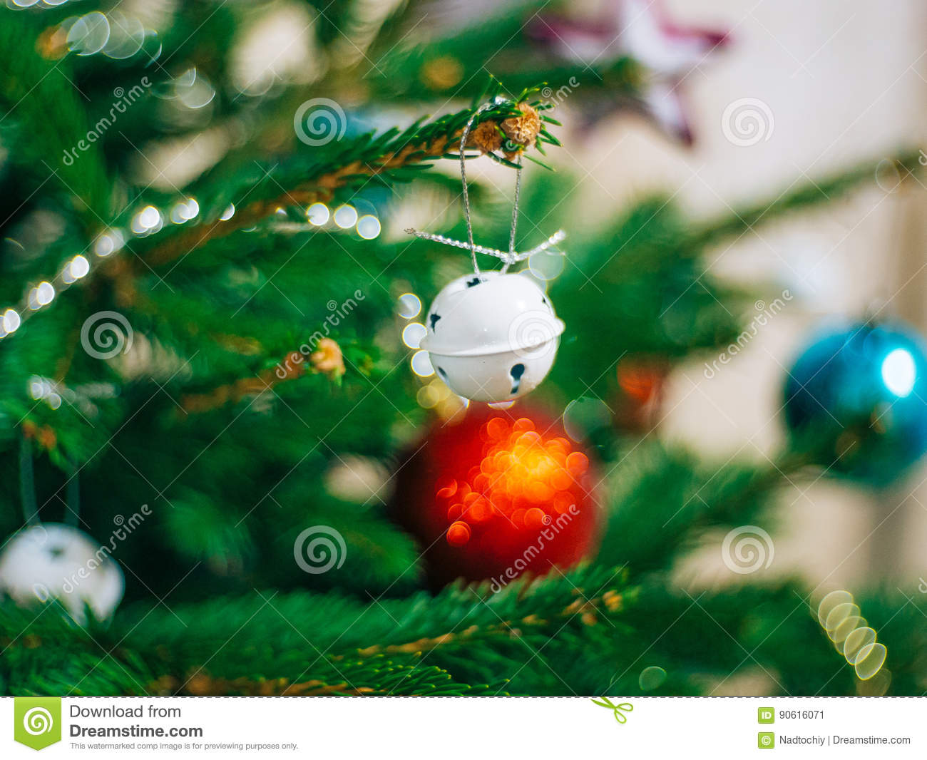 a small christmas tree in a pot decorated with balls garlands and lights