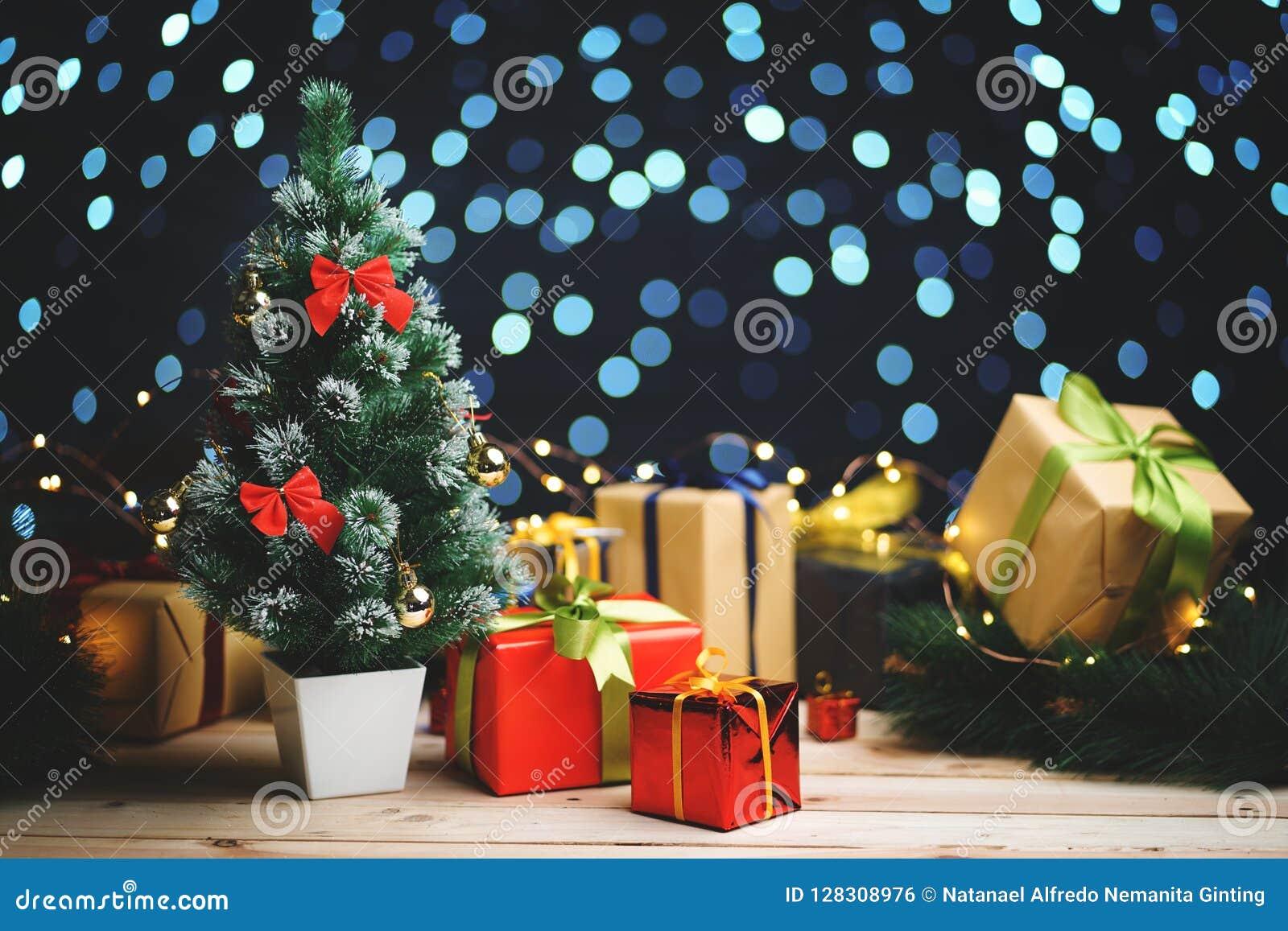 Small Christmas Tree Between Christmas Presents Against Beautifull Blue Lights Bokeh